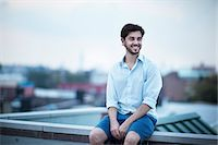 Young smiling man looking away Stock Photo - Premium Royalty-Freenull, Code: 6102-06471239
