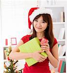Asian Christmas woman with gift, indoor / inside house. Stock Photo - Royalty-Free, Artist: szefei                        , Code: 400-06477678