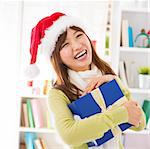 Asian female holding her Christmas gift smiling happily, indoor/inside house. Stock Photo - Royalty-Free, Artist: szefei                        , Code: 400-06477684