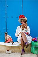 Woman Smoking Cigar and Sitting on Curb with Cat Wearing Costume, Old Havana, Havana, Cuba Stock Photo - Premium Rights-Managednull, Code: 700-06486581