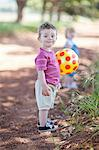 Toddler boy with ball on dirt road Stock Photo - Premium Royalty-Free, Artist: ableimages, Code: 649-06488481