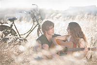Woman playing guitar for boyfriend Stock Photo - Premium Royalty-Freenull, Code: 649-06488544