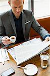 Businessman reading in cafe Stock Photo - Premium Royalty-Free, Artist: Cultura RM, Code: 649-06488875