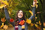 Woman playing in autumn leaves Stock Photo - Premium Royalty-Free, Artist: Cultura RM, Code: 649-06488908