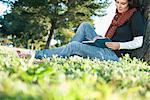Woman reading book in grass Stock Photo - Premium Royalty-Free, Artist: Blend Images, Code: 649-06489060
