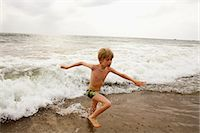 Boy playing in waves on beach Stock Photo - Premium Royalty-Freenull, Code: 649-06489238