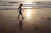 Boy walking in waves on beach Stock Photo - Premium Royalty-Freenull, Code: 649-06489241