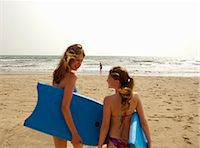 Girls carrying boogie boards on beach Stock Photo - Premium Royalty-Freenull, Code: 649-06489244