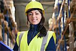 Smiling worker standing in warehouse Stock Photo - Premium Royalty-Free, Artist: Blend Images, Code: 649-06489252