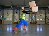 Worker balancing boxes in warehouse Stock Photo - Premium Royalty-Freenull, Code: 649-06489258