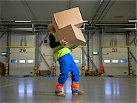 Worker carrying boxes in warehouse Stock Photo - Premium Royalty-Freenull, Code: 649-06489259