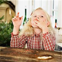 Girl eating Christmas cookies in kitchen Stock Photo - Premium Royalty-Freenull, Code: 649-06489289