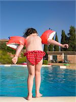 Girl in floaters at swimming pool Stock Photo - Premium Royalty-Freenull, Code: 649-06489398