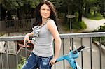 Woman leaning on scooter on city street Stock Photo - Premium Royalty-Free, Artist: Albert Normandin, Code: 649-06489411