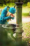Woman drinking from water fountain Stock Photo - Premium Royalty-Free, Artist: Raymond Forbes, Code: 649-06489654