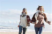 Smiling women running on beach Stock Photo - Premium Royalty-Freenull, Code: 649-06489713
