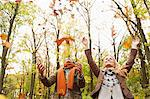 Smiling couple playing in autumn leaves Stock Photo - Premium Royalty-Free, Artist: Ikon Images, Code: 649-06489798