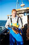 Fisherman holding lobster on boat Stock Photo - Premium Royalty-Free, Artist: Westend61, Code: 649-06489858