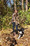 Woman walking dog in forest Stock Photo - Premium Royalty-Free, Artist: Blend Images, Code: 649-06489919