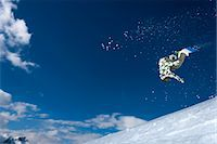 sports and snowboarding - Snowboarder jumping on snowy slope Stock Photo - Premium Royalty-Freenull, Code: 649-06490023