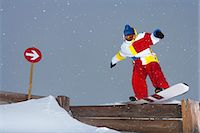 sports and snowboarding - Snowboarder sliding on wooden fence Stock Photo - Premium Royalty-Freenull, Code: 649-06490026