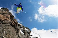 Snowboarder jumping on rocky slope Stock Photo - Premium Royalty-Freenull, Code: 649-06490041