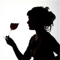 Silhouette portrait of a young woman enjoying a glass of red wine Stock Photo - Premium Rights-Managednull, Code: 824-06492132