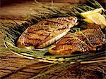 Grilled Trout on Sea Grass; Lemon Wedges Stock Photo - Premium Royalty-Freenull, Code: 659-06494481