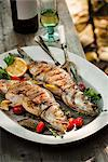 Two Whole Grilled Stuffed Branzino Fish on a Platter; On an Outdoor Table Stock Photo - Premium Royalty-Freenull, Code: 659-06495114