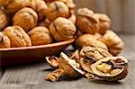 Whole and halved walnuts on a wooden table Stock Photo - Premium Royalty-Free, Artist: Photocuisine, Code: 659-06495387