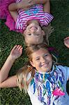 sisters laying on grass head to head Stock Photo - Premium Royalty-Freenull, Code: 6106-06497367