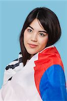 filipina - Patriotic young woman wrapped in Korean flag over blue background Stock Photo - Premium Royalty-Freenull, Code: 693-06497570