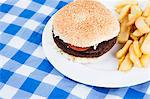 Close-up of hamburger and French fries on table Stock Photo - Premium Royalty-Free, Artist: Michael Mahovlich, Code: 693-06497618
