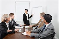 Young woman using whiteboard in business meeting Stock Photo - Premium Royalty-Freenull, Code: 693-06497669