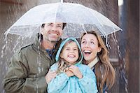 people with umbrellas in the rain - Enthusiastic family under umbrella in downpour Stock Photo - Premium Royalty-Freenull, Code: 6113-06498045