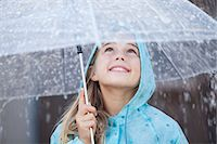 people with umbrellas in the rain - Close up of smiling girl under umbrella in downpour Stock Photo - Premium Royalty-Freenull, Code: 6113-06498070