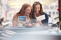 Laughing friends looking at postcards at sidewalk cafe Stock Photo - Premium Royalty-Freenull, Code: 6113-06498082