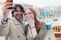 Laughing couple taking self-portrait with camera phone in Venice Stock Photo - Premium Royalty-Freenull, Code: 6113-06498084