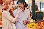 Smiling couple tasting fruit in market Stock Photo - Premium Royalty-Free, Artist: Cultura RM, Code: 6113-06498091