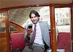 Portrait of smiling businessman with cell phone on boat in Venice Stock Photo - Premium Royalty-Free, Artist: Albert Normandin, Code: 6113-06498238