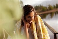 Smiling woman wrapped in blanket at lakeside Stock Photo - Premium Royalty-Freenull, Code: 6113-06498475