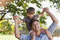 Smiling father carrying son on shoulders under tree Stock Photo - Premium Royalty-Freenull, Code: 6113-06498492