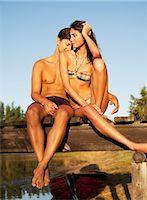 Serene couple sitting at edge of dock over lake Stock Photo - Premium Royalty-Freenull, Code: 6113-06498548