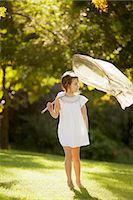 Girl carrying butterfly net in grass Stock Photo - Premium Royalty-Freenull, Code: 6113-06498571