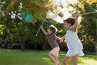 Happy boy and girl holding hands and running with butterfly nets in grass Stock Photo - Premium Royalty-Freenull, Code: 6113-06498575