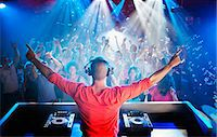 DJ with arms outstretched overlooking dance floor Stock Photo - Premium Royalty-Freenull, Code: 6113-06498596