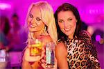 Portrait of smiling women toasting cocktails at nightclub Stock Photo - Premium Royalty-Free, Artist: Blend Images, Code: 6113-06498610