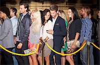 queue club - Couple with cell phone standing in queue outside nightclub Stock Photo - Premium Royalty-Freenull, Code: 6113-06498613