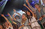 Enthusiastic crowd with arms raised behind railing at concert Stock Photo - Premium Royalty-Free, Artist: Blend Images, Code: 6113-06498646