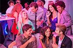Smiling friends drinking champagne in nightclub Stock Photo - Premium Royalty-Free, Artist: Blend Images, Code: 6113-06498655